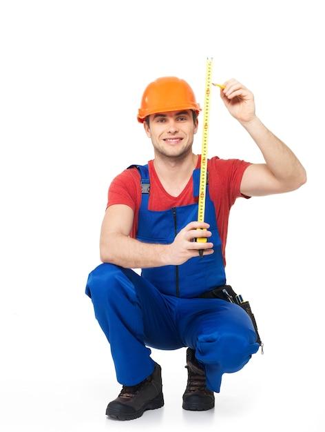 Trabalhador da construção civil medindo a parede sobre fundo branco - imagens do trabalhador manual. Foto gratuita