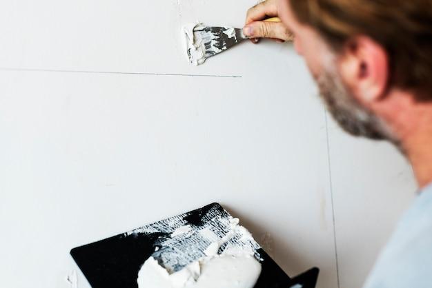 Trabalhador da construção civil pintando a parede Foto gratuita