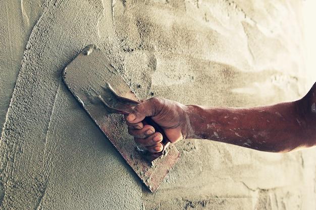 Trabalhador da construção civil reboco de cimento na parede Foto Premium