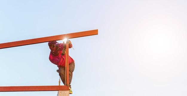 Trabalhador da construção civil soldagem de aço para estrutura de telhado Foto Premium