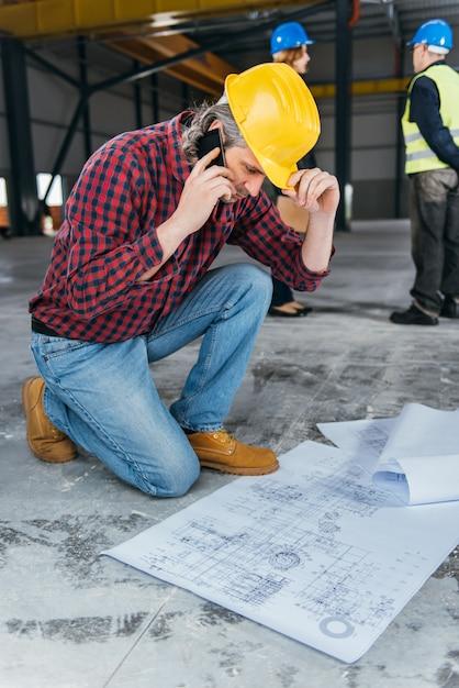 Trabalhador da construção civil verificando blueprints e falando ao telefone Foto Premium