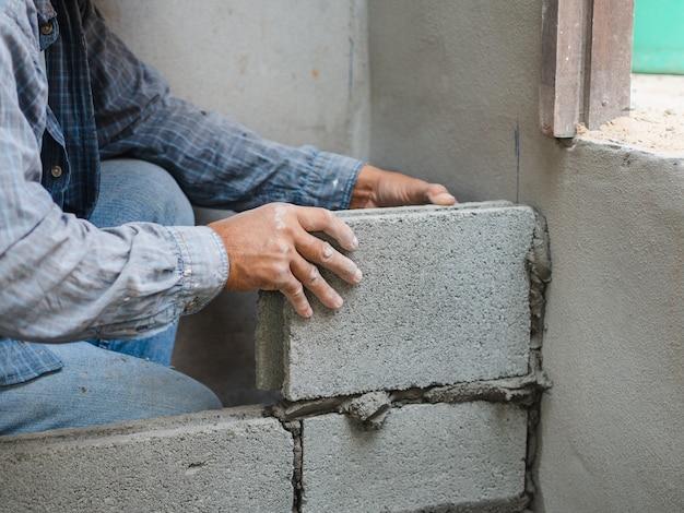 Trabalhador da construção profissional que coloca tijolos com cimento. Foto Premium