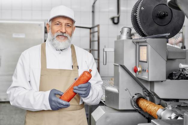 Trabalhador da fábrica de carne segurando salsicha, posando. Foto Premium