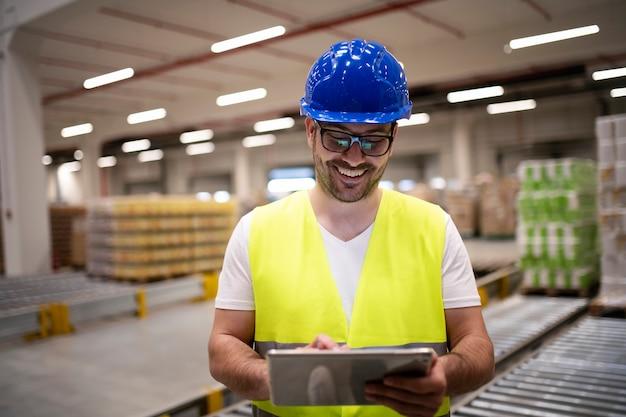 Trabalhador da indústria com jaqueta reflexiva e capacete de segurança olhando para um tablet no interior de uma fábrica moderna Foto gratuita