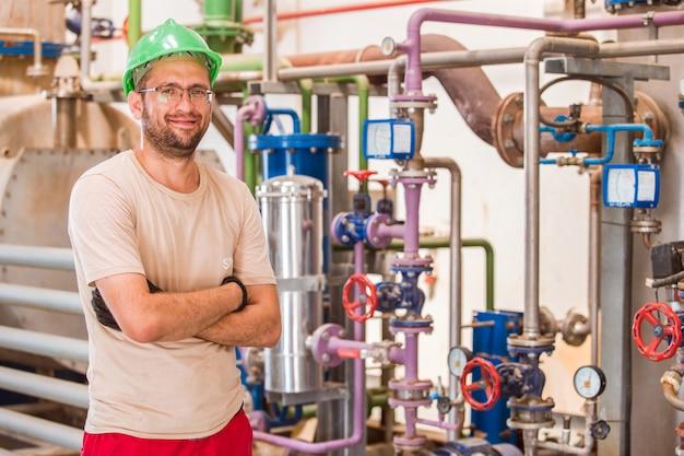Trabalhador da indústria posando dentro da fábrica com barras e canos ao redor Foto gratuita