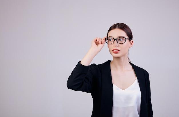 Trabalhador da semana. mulher de negócios de aparência agradável, olhando de lado e de pé em cinza em uma jaqueta preta, camiseta branca e óculos de pc. as mãos da mulher seguram as bordas dos óculos. Foto Premium