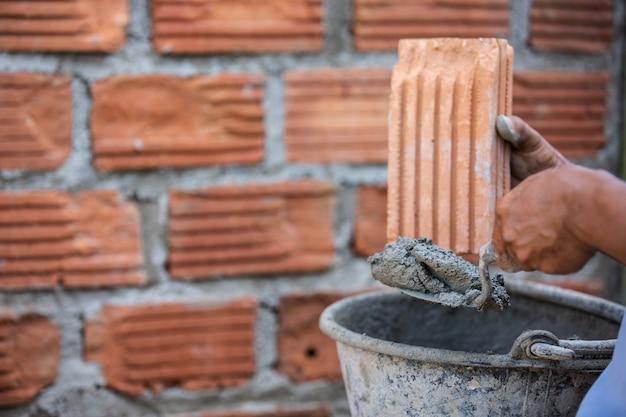 Trabalhador de alvenaria na parede exterior com uma faca da pá de pedreiro. Foto gratuita