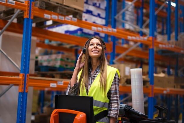Trabalhador de armazém atraente recebendo instruções por meio de equipamento de fone de ouvido Foto gratuita