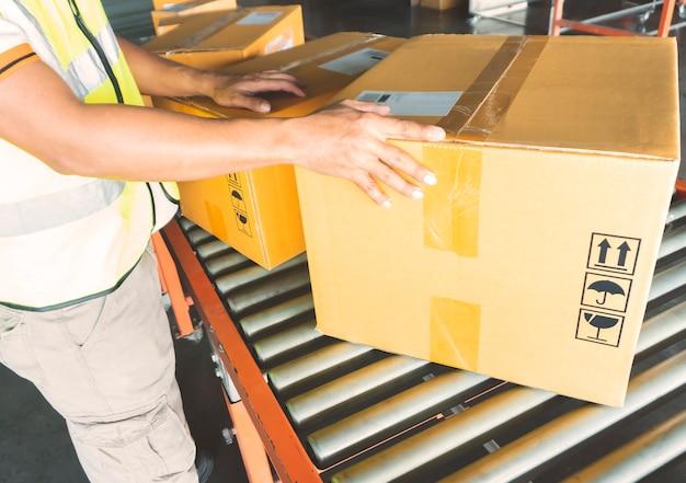 Trabalhador de armazém, classificando as caixas de embalagem na correia transportadora de rolos Foto Premium
