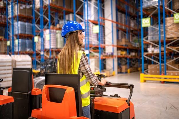 Trabalhador de armazém em roupa de trabalho protetora dirigindo empilhadeira e manipulando mercadorias em instalação de armazenamento Foto gratuita