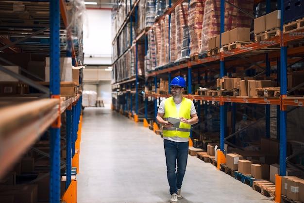 Trabalhador de armazém olhando para prateleiras com pacotes e caminhando pela grande área de distribuição de armazenamento de armazém Foto gratuita