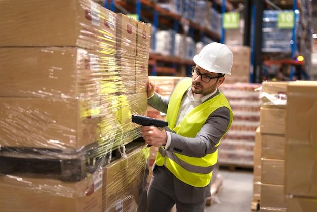 Trabalhador de armazém usando leitor de código de barras para analisar mercadorias recém-chegadas para posterior colocação no departamento de armazenamento Foto gratuita