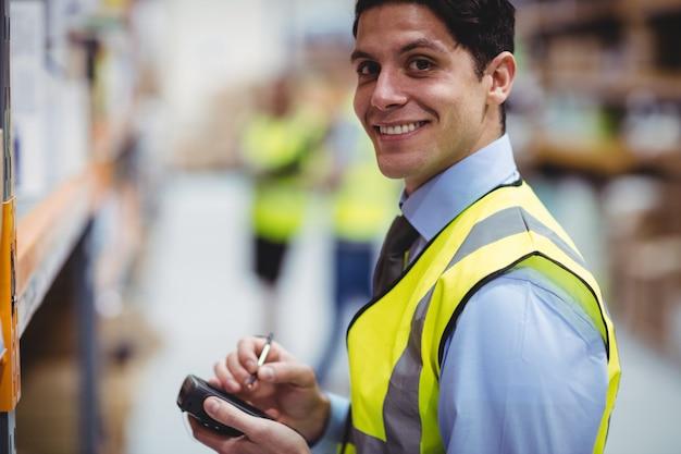 Trabalhador de armazém, usando o scanner de mão no armazém Foto Premium