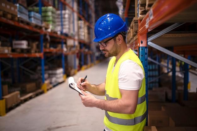 Trabalhador de armazém verificando estoque em grande centro de distribuição Foto gratuita