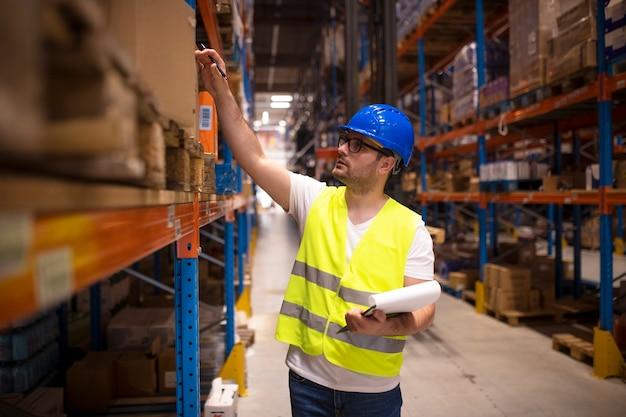 Trabalhador de armazém verificando o estoque em um grande armazém de distribuição Foto gratuita
