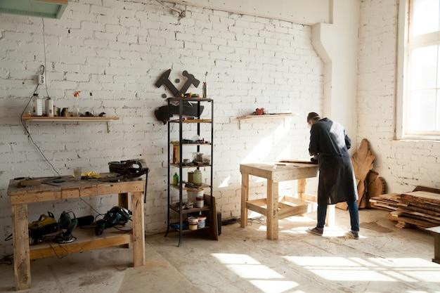 Trabalhador de carpintaria trabalhando em bancada em carpintaria pequena Foto gratuita