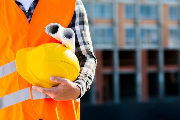 Trabalhador de construção de close-up segurando o capacete Foto gratuita