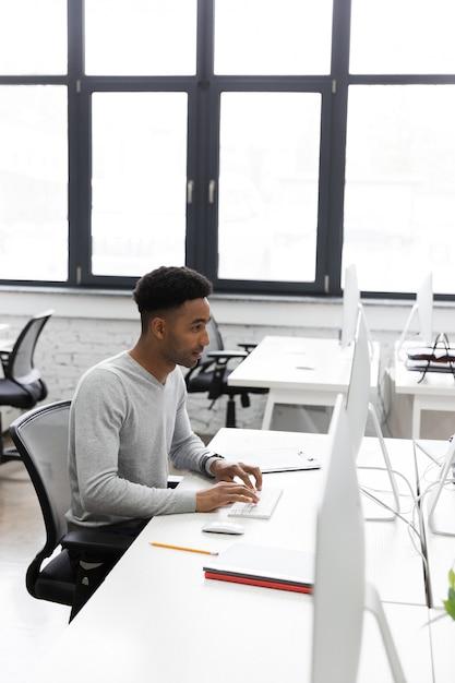 Trabalhador de escritório africano jovem sentado em uma mesa Foto gratuita