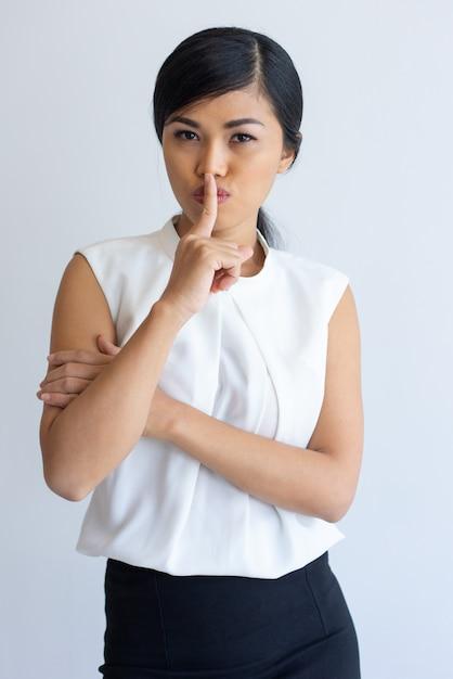 Trabalhador de escritório asiático sério mantendo segredo Foto gratuita