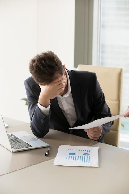 Trabalhador de escritório cansado, ficando mais e mais trabalho Foto gratuita