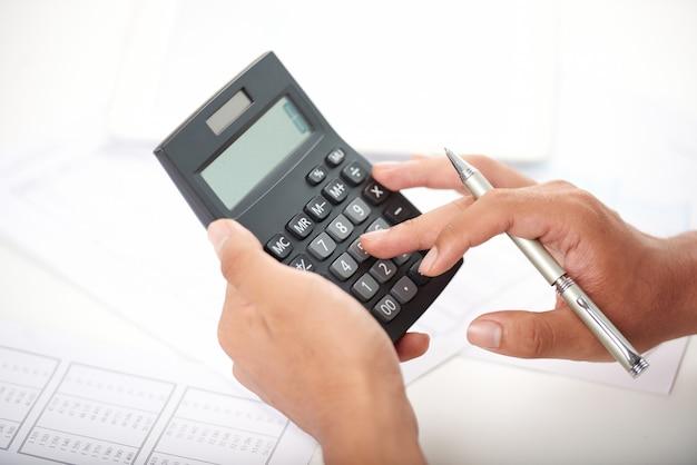 Trabalhador de escritório irreconhecível usando calculadora Foto gratuita