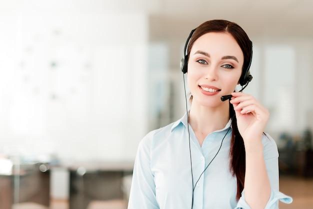 Trabalhador de escritório novo de sorriso com uns auriculares que respondem em um centro de chamadas, mulher que fala com os clientes. retrato de um cliente atraente e representante de suporte técnico Foto Premium