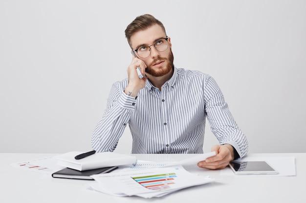 Trabalhador de escritório ocupado liga para parceiro de negócios para discutir reunião futura Foto gratuita