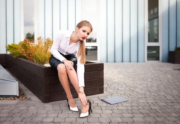 Trabalhador de escritório sente dor nas pernas de saltos. empregado cansado sofre de dor nas articulações Foto Premium