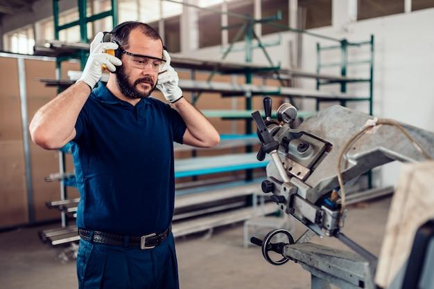 Trabalhador de máquina de corte de serra de fita colocando protetores de orelha Foto Premium