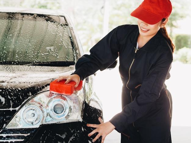 Trabalhador de mulher asiática lavar carro na garagem Foto Premium