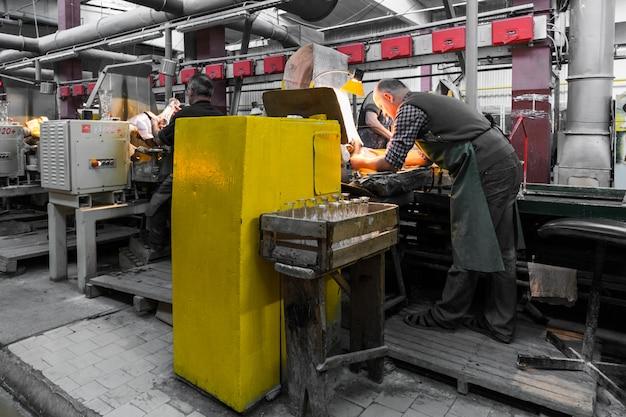 Trabalhador de produção de vidro trabalhando com equipamentos da indústria na fábrica Foto Premium