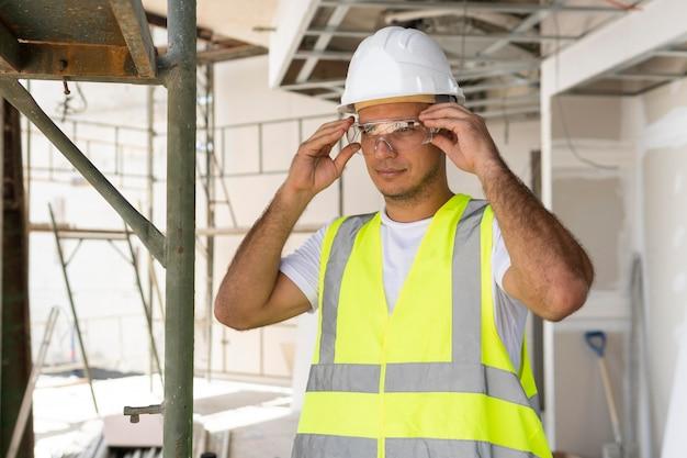 Trabalhador de visão frontal na construção usando equipamento de proteção Foto gratuita