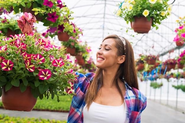 Trabalhador de viveiro florista segurando flores em vasos e sorrindo no centro do jardim Foto gratuita