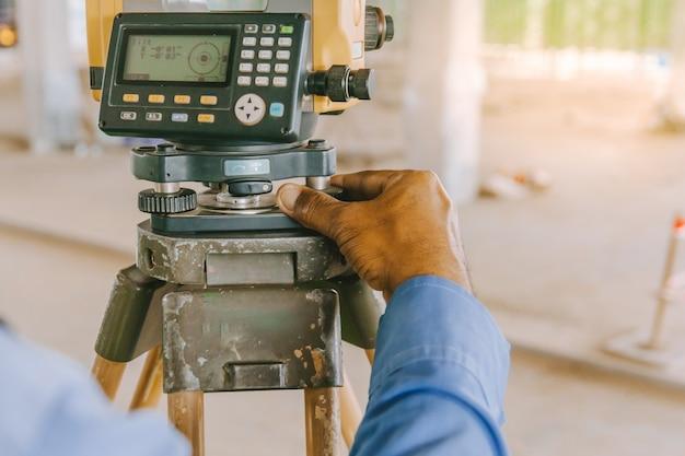Trabalhador do coordenador do topógrafo que faz a medição com equipamento do teodolito no canteiro de obras. Foto Premium
