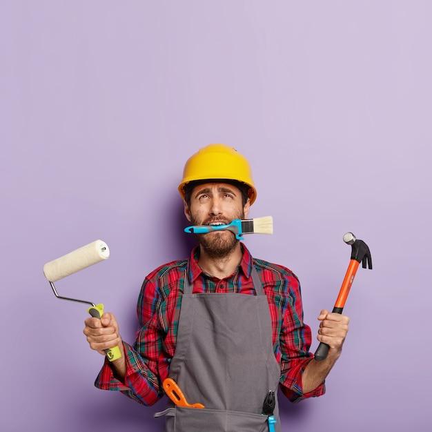 Trabalhador do sexo masculino de reparos domésticos ocupado com a reforma da casa, guarda equipamentos de construção Foto gratuita