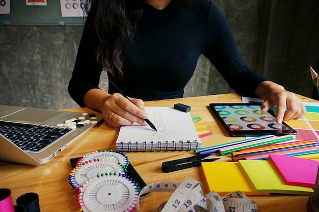 Trabalhador elegante de designer de moda como esboço de nova coleção em ateliê. conceito de design criativo Foto Premium