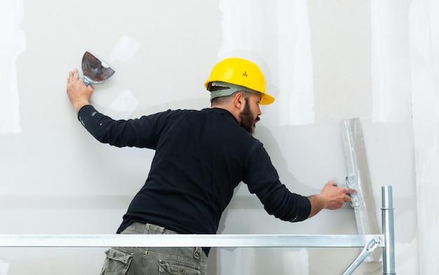 Trabalhador emplastrando a parede da placa de gipsita. Foto Premium