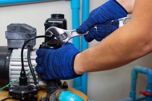 Trabalhador engenheiro manutenção reparo gasget valor da bomba de água Foto Premium