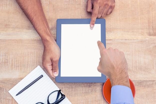 Trabalhador ensinando outra coisa trabalhador no tablet Foto gratuita