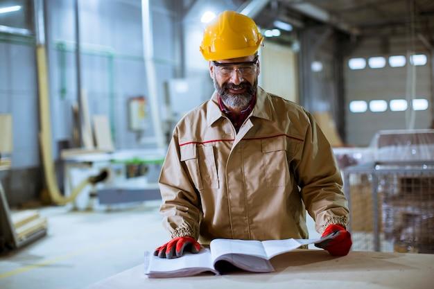 Trabalhador envelhecido médio considerável que verifica a documentação na fábrica Foto Premium