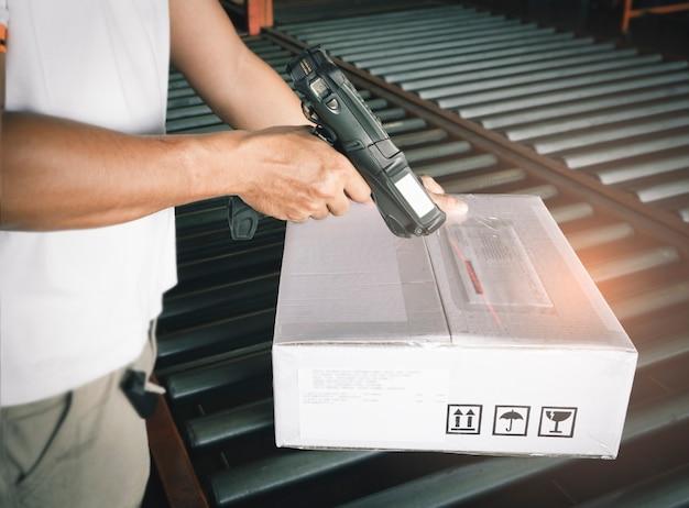 Trabalhador, escaneamento de scanner de código de barras com caixas de remessa na correia transportadora. Foto Premium