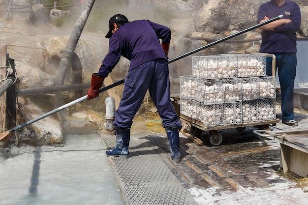 Trabalhador está fervendo ovos em água mineral no vale de owakudani Foto Premium