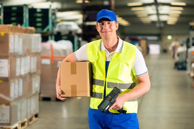 Trabalhador faz a varredura do pacote no armazém de encaminhamento Foto Premium
