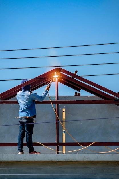 Trabalhador, ficar, topo telhado, e, soldadura, estrutura, de, casa, em, local construção Foto Premium