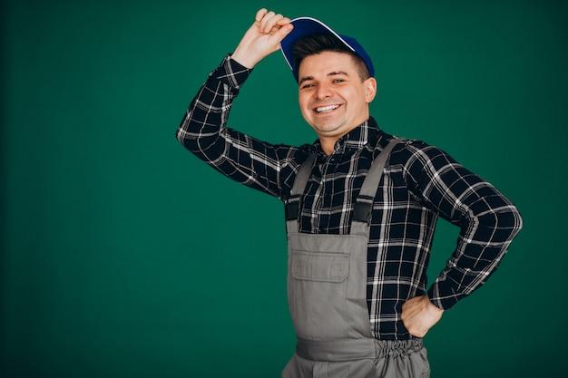 Trabalhador homem de chapéu isolado na parede verde Foto gratuita