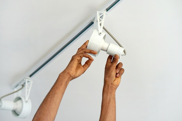 Trabalhador homem eletricista africano instalar um teto led holofotes Foto Premium