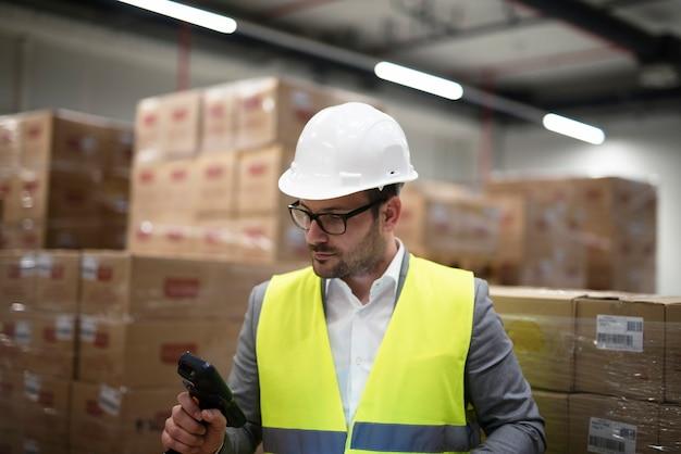 Trabalhador industrial com leitor de código de barras rastreando e controlando mercadorias que chegam ao depósito Foto gratuita