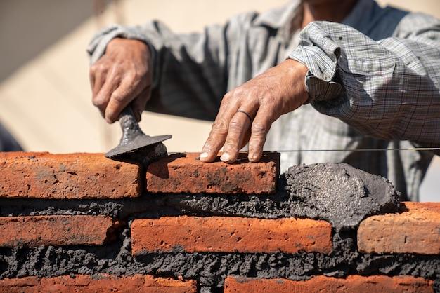 Trabalhador industrial de pedreiro instalar alvenaria de tijolo com espátula espátula no canteiro de obras Foto Premium