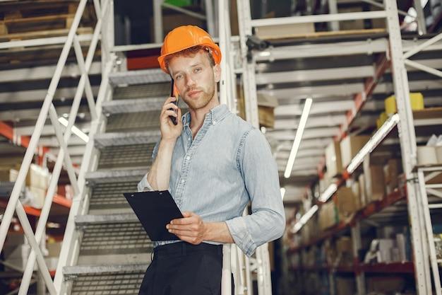 Trabalhador industrial dentro de casa na fábrica. empresário com capacete laranja. homem de camisa azul. Foto gratuita