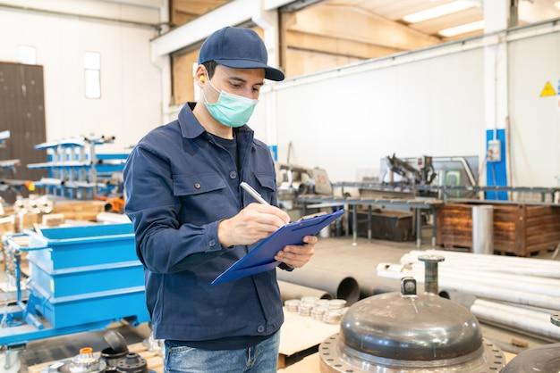Trabalhador industrial, escrevendo em um documento em uma fábrica Foto Premium